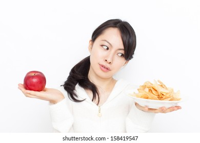 beautiful young woman choosing between apple and potato chips