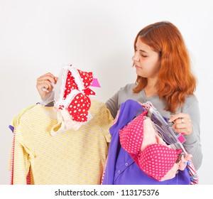 Beautiful young woman choosing clothes