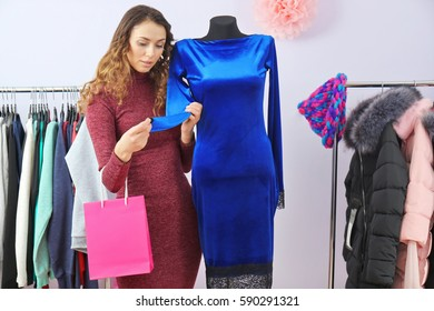 Beautiful young woman choosing clothes in modern shop