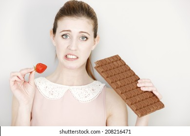 Beautiful young woman choosing to eat chocolate or a fresh strawberry.