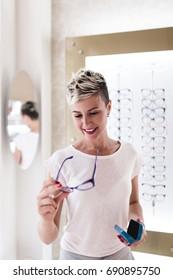 Beautiful young woman choosing eyeglasses frame in optical store.