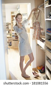 beautiful young woman choosing her clothes in the morning on a sunny day