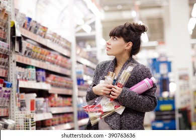 Beautiful young woman choosing paint colors and brushes at hardware store or hobby market. Young lady is shopping in the shop with do-it-yourself goods.