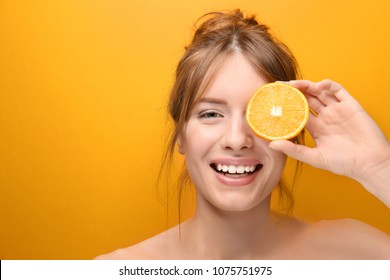 Beautiful young woman with citrus fruit on color background