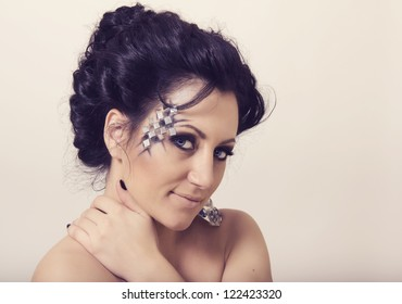 Beautiful young woman with classical hairstyle and creative make up
