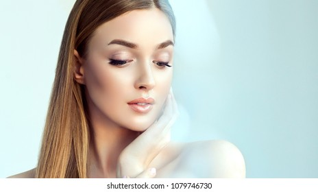 Beautiful young woman with clean fresh skin  .Beauty face  care. Facial  treatment   . Girl in a gentle blue light and glare. Cosmetology and Spa