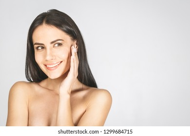 Beautiful Young Woman with Clean Fresh Skin looking down. Girl beauty face care. Facial treatment. Cosmetology, beauty and spa. Isolated over white.