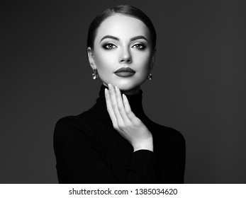 Beautiful Young Woman with Clean Fresh Skin. Perfect Makeup. Beauty Fashion. Plump Lips. Cosmetic Eyeshadow. Smooth Hair. Girl in Black Turtleneck. Black and white photo