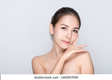 Beautiful young woman with clean fresh skin, Hair sleek, Proposing a product. Gestures for advertisement on gray background, Front view, with copy space.