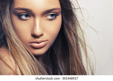 Beautiful young woman with clean fresh skin. Close up portrait, studio shot. Horizontal.