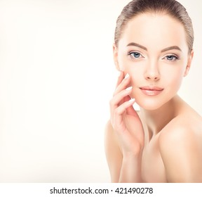 Beautiful Young Woman with Clean Fresh Skin  touch her face . Facial  treatment   . Cosmetology , beauty  and spa .