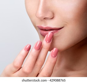 Beautiful Young Woman with Clean Fresh Skin. Close up Portrait.  Fashion Model Girl Face. Perfect Skin. Professional Makeup. Fashion shiny highlighter on skin, sexy gloss lips. Perfect manicure.