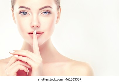 Beautiful Young Woman with Clean Fresh Skin  touch her lips. Facial  treatment   . Cosmetology , beauty  and spa . A secret or a surprise ,the model holds a finger to her mouth