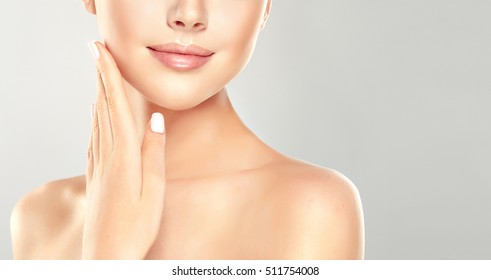 Beautiful Young Woman with Clean Fresh Skin close up . Skin care face . Cosmetology , girl washes his face .