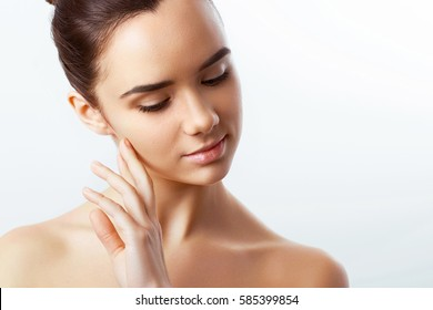 Beautiful Young Woman with Clean Fresh Skin touch own face. Cosmetology, beauty and spa.