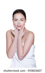 Beautiful Young Woman with Clean Fresh Skin Touch Face. Beautiful Female Face, Girl gets Facial Treatment, Spa therapy and youthfulness of the skin of the Face. Beauty Spa, Girl on a light Background