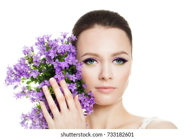 Beautiful Young Woman with Clean Fresh Skin, Makeup and Flowers Isolated on White Background. Beauty, Facial Treatment and Cosmetology