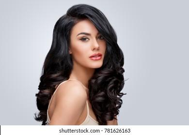 Schöne junge Frau mit sauberen, gesunden, lockigen Haaren