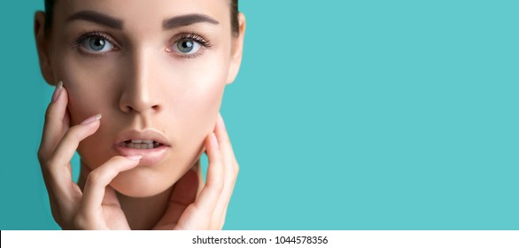 Beautiful young woman with clean perfect skin. Portrait of beauty model with natural nude make up. Spa, skincare and wellness. Close up, background, copyspace.