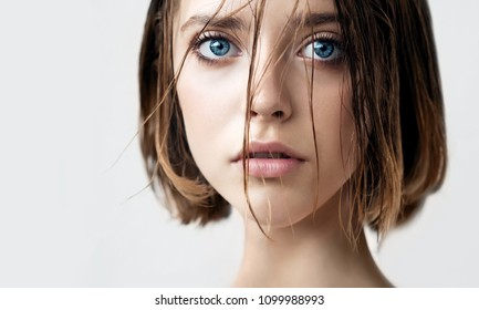 Beautiful young woman with clean perfect skin and wet hair. Portrait of beauty model with natural nude makeup moisturizing her skin. Spa, skincare and wellness. Close up, background, copy space.
