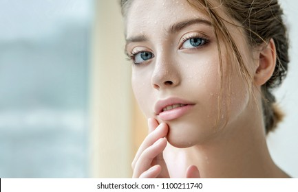 Beautiful young woman with clean perfect skin and water moisture drops touching face. Portrait of beauty model with natural nude makeup moisturizing her skin. Spa, skincare and wellness.