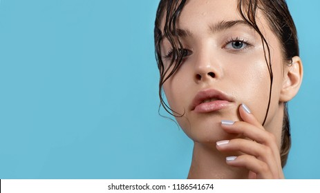 Beautiful young woman with clean perfect skin and water moisture drops touching face. Portrait of beauty model with natural nude makeup moisturizing her skin by lotion. Spa, skincare and wellness.