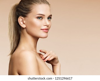 Beautiful young woman with clean perfect skin on beige background. Youth and skin care concept