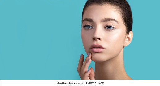 Beautiful young woman with clean perfect skin and water moisture drops touching face. Spa, skincare and wellness. Close up, background, copy space.