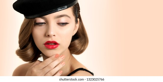 Beautiful young woman with clean perfect skin touching her face, Portrait of beauty model with classic make up and red lips, bob hair and beret hat. Retro style.