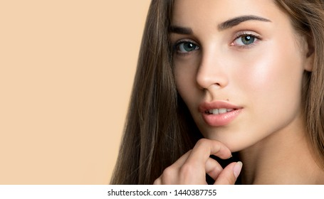 Schöne junge Frau mit sauberer, perfekt frischer Haut, die ihr Gesicht berührt. Porträt des Schönheitsmodells mit natürlicher Schminke, geformten Augenbrauen und langen Wimpern. Spa, Hautpflege und Wellness.