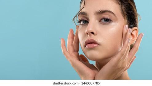 Schöne junge Frau mit sauberer, perfekt frischer Haut sieht auf. Porträt des Schönheitsmodells mit natürlicher Schminke, geformten Augenbrauen und langen Wimpern. Spa, Hautpflege und Wellness.