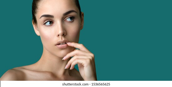 Beautiful young  woman with clean perfect fresh skin touching her facee. Portrait of beauty model with natural make up, formed eyebrows  and long eyelashes.  Spa, skincare and wellness.