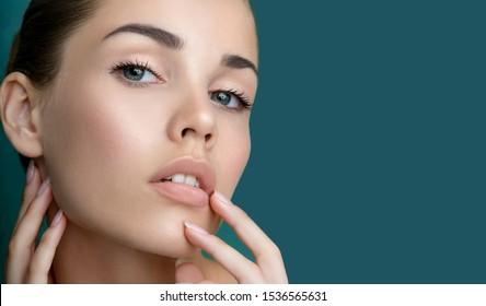 Schöne junge Frau mit sauberer, perfekt frischer Haut, die ihr Gesicht berührt, einzeln auf Blau. Porträt des Schönheitsmodells mit natürlicher Schminke, geformten Augenbrauen und langen Wimpern.