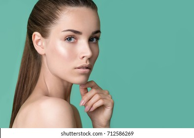 Beautiful young woman with clean perfect skin. Portrait of beauty model with natural nude make up and touching face. Spa, skincare and wellness. Close up, light green background, copyspace.
