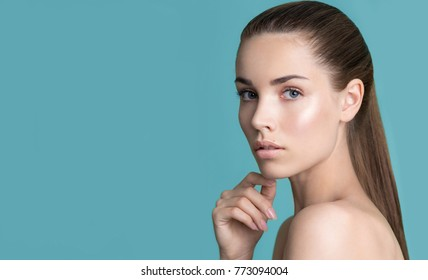 Beautiful young woman with clean perfect skin and hand with manicure touching face. Portrait of beauty model with natural nude make up. Spa, skincare and wellness. Close up, background, copyspace.