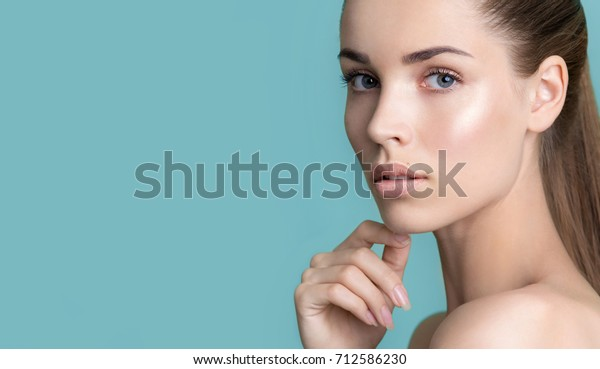 Beautiful young woman with clean perfect skin. Portrait of beauty model with natural nude make up and touching her face. Spa, skincare and wellness. Close up, blue background, copyspace.