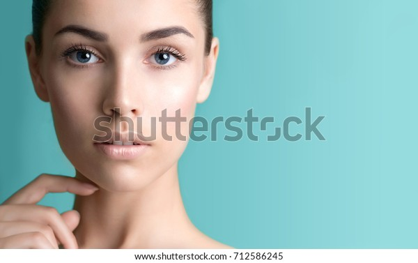 Beautiful young woman with clean perfect skin. Portrait of beauty model with natural nude make up and long eyelashes. Spa, skincare and wellness. Close up, background, copyspace.