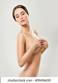 Beautiful young woman with clean skin nude topless breasts. Beautiful woman covering her nude breast.