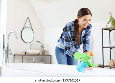 Beautiful young woman cleaning bathroom