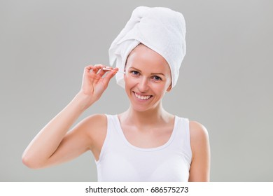 Beautiful young woman cleaning ears on gray background.Ear hygiene