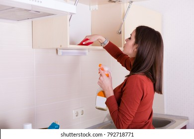 Beautiful young woman cleaning her apartment kitchen