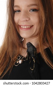 A beautiful young woman in a close up image with long brunette hairhaving a fake black bird on her dress, isolated for white background