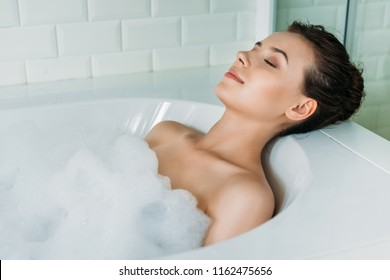 beautiful young woman with closed eyes relaxing in bathtub with foam