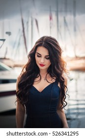Beautiful young woman with closed eyes and long dark hair and red lips portrait sea yacht and boats background