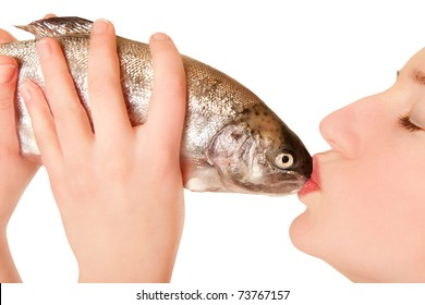 Beautiful young woman with closed eyes kissing a fish, isolated on white