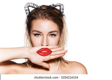 Beautiful young woman closes her lips with hand. Funny girl looks like a cat with artificial lips on her face. Studio closeup portrait on white background.
