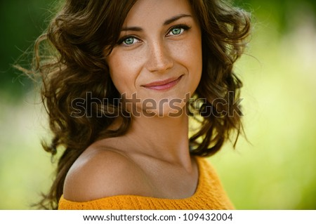 Beautiful young woman close-up in orange sweater, against green of summer park.