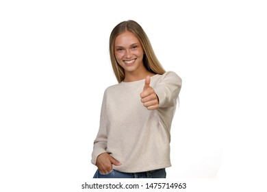 Beautiful young woman clothed casually, smiles and shows thumbs up