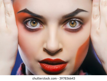 Beautiful young woman with color art makeup.
