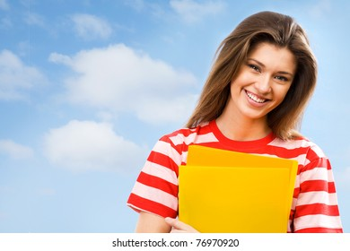 The beautiful young woman with color folders in hands